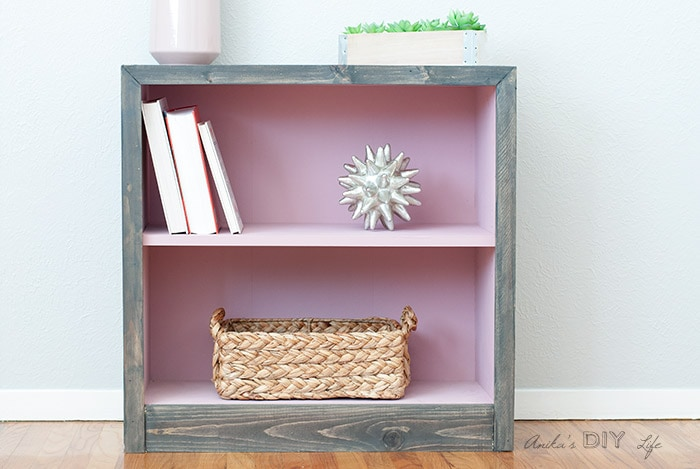 Pink and grey laminate bookshelf makeover - the after. Interior is pink and the outside with grey peel and stick barn wood tile.