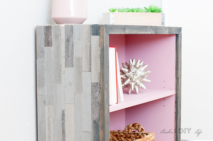 laminate bookshelf makeover with grey barn wood tile on the outside.