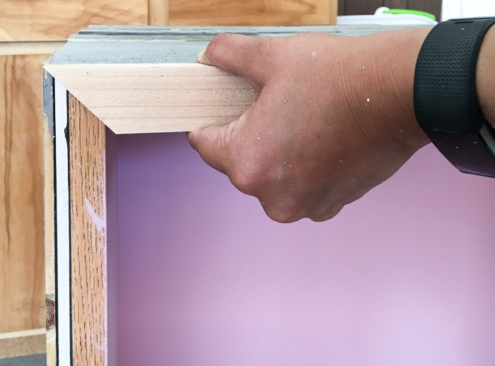 Attaching trim to the DIY weathered barn wood bookshelf