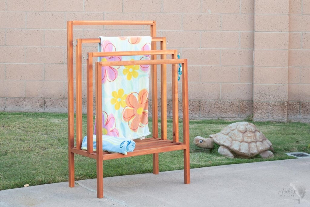 Redwood towel rack in backyard with colorful towel on it.