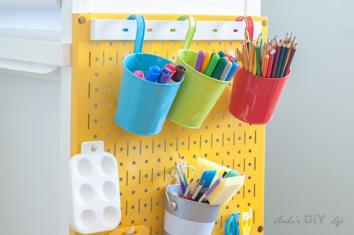 Close up of yellow Wall control metal pegboard system used in a DIY kids art station