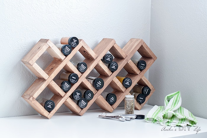 DIY spice rack filled with spice bottles on a white contertop