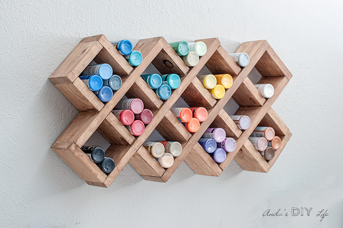 DIY spice rack hanging on the wall filled with craft paint bottles