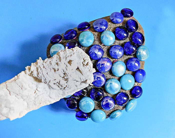 Applying grout over gems to create a mosaic rock