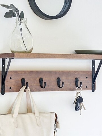 How to build your own DIY entryway shelf with hooks underneath. This easy to build entryway shelf is perfect for organization and makes great wall decor too!