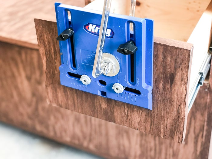 using a hardware jig to add the drawer knob or pull.