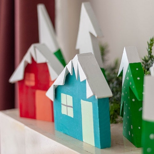 See how you can make a DIY Christmas village using scrap wood. This bright and happy Christmas village display is an easy project!