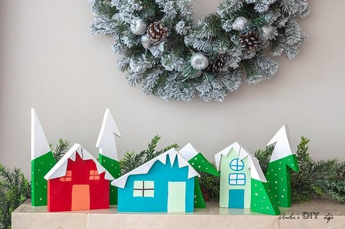Full display of DIY Christmas Village using scrap wood on mantle