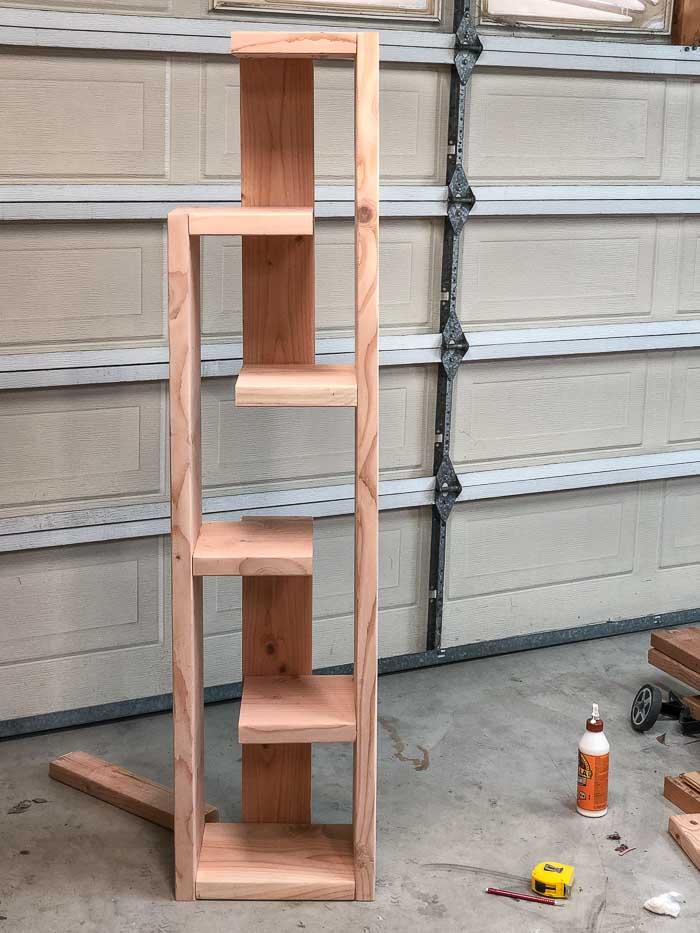 Complete DIY modern bookshelf before staining in a garage