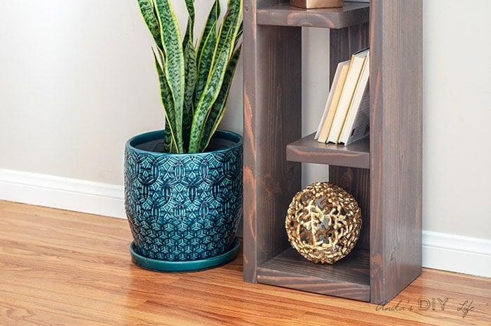 Close up of bottom of DIY modern bookshelf with decor items.