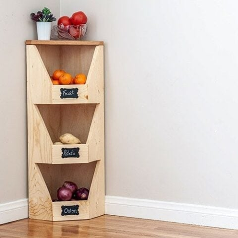 DIY corner vegetable storage bin with veggies and fruits in it.