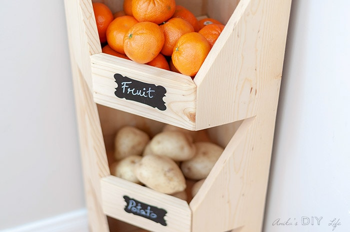close up of corner vegetable storage bin with oranges and chalkboard label