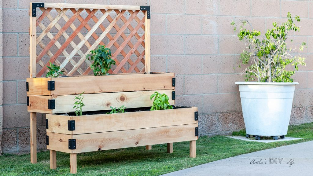DIY Tiered raised vegetable bed with legs and trellis in backyard with vegetable plants