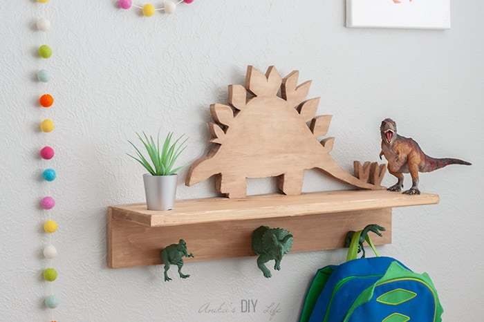 DIY Dinosaur shelf with dinosaur hooks on the wall with backpack hanging
