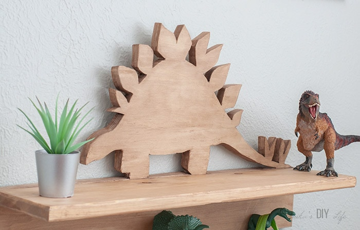 Close up of Wooden dinosaur cutout on DIY dinosaur shelf
