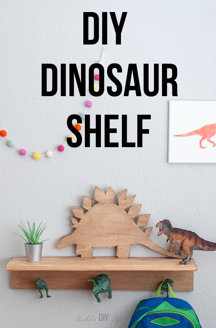 Wooden DIY dinosaur shelf with hooks with backpack and text overlay.