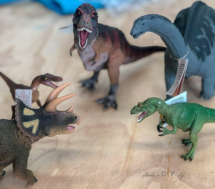 Plastic dinosaurs on wooden bench