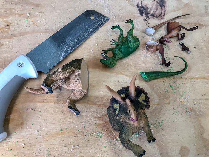 Dinosaur with their backs cut off using a hand saw for the DIY Dinosaur shelf