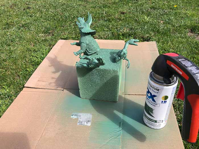 Spray painting dinosaurs green outdoors for the DIY Dinosaur shelf