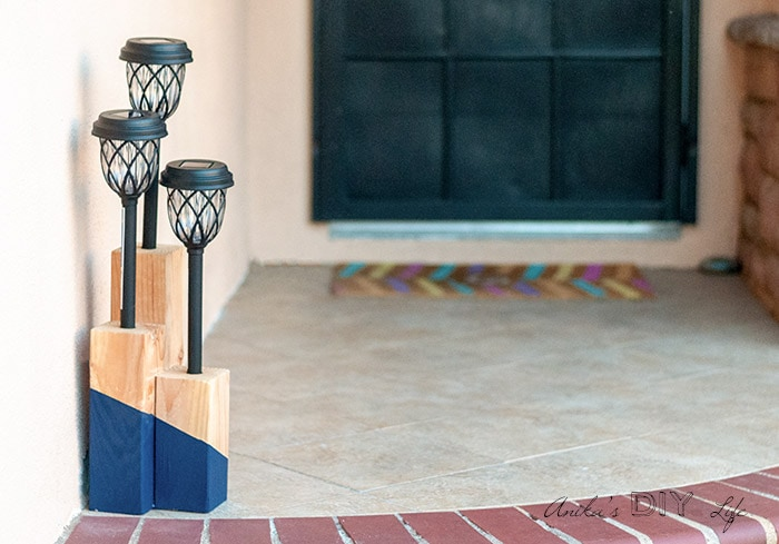 DIY solar light post with blue paint on front steps
