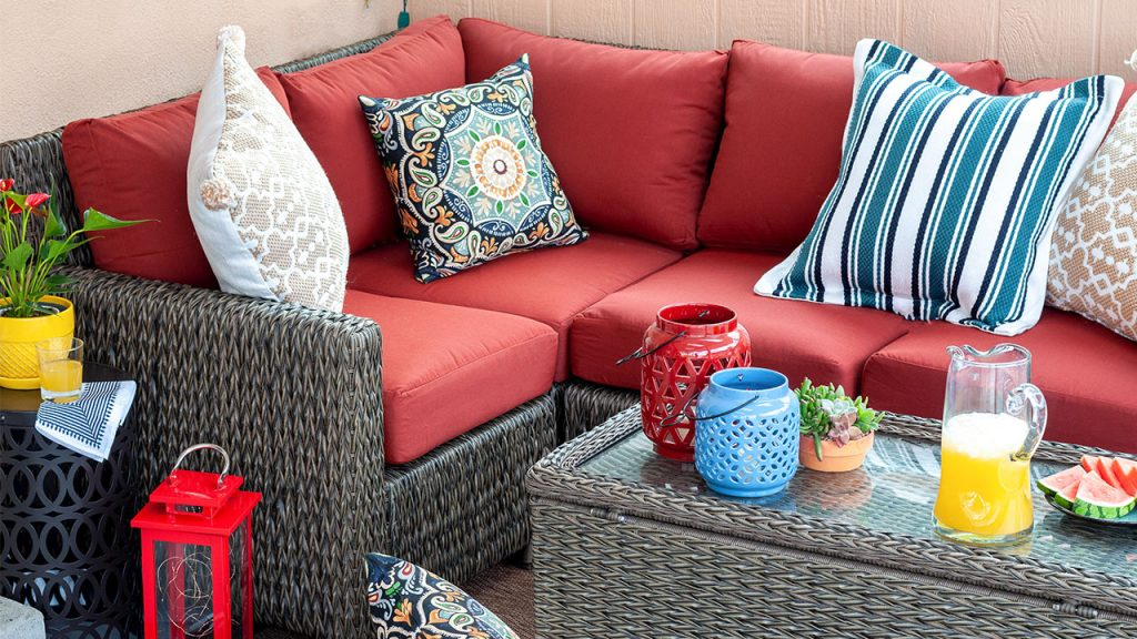 Full view of small patio decorating ideas - red sectional, blue planter and lights