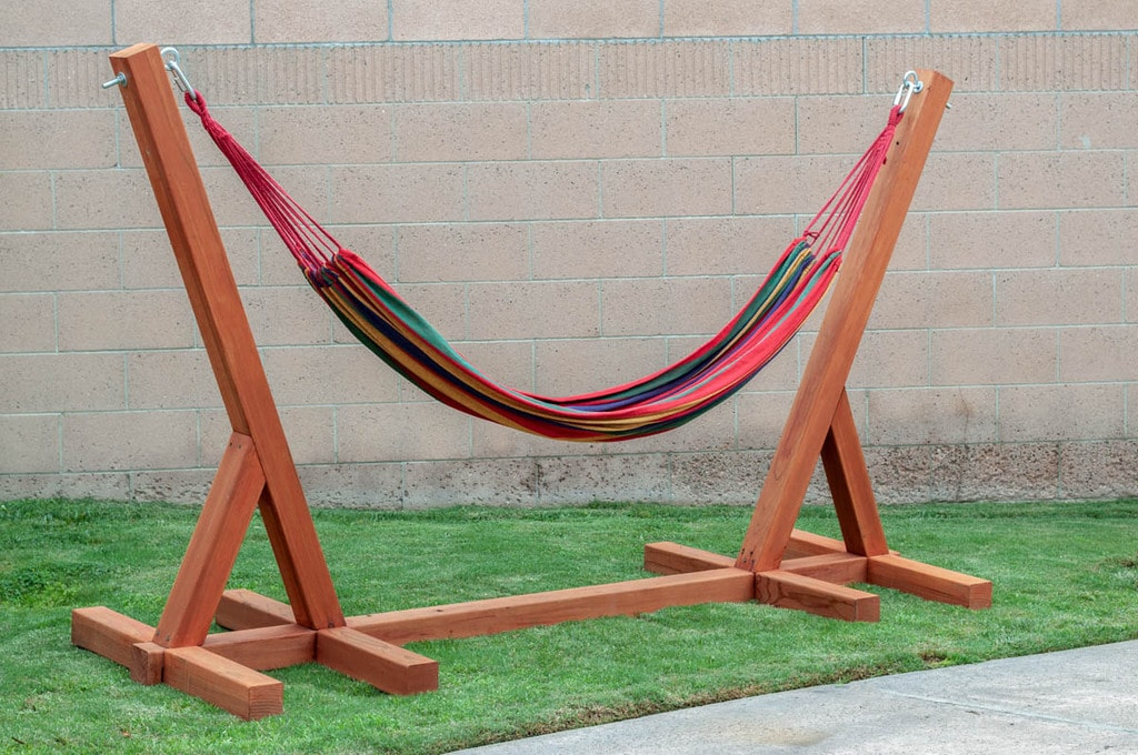 DIY Hammock stand made with wood with a colorful hammock on it.