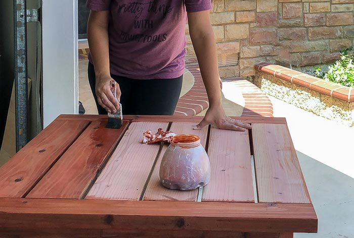 Staining the DIY outdoor table with redwood stain