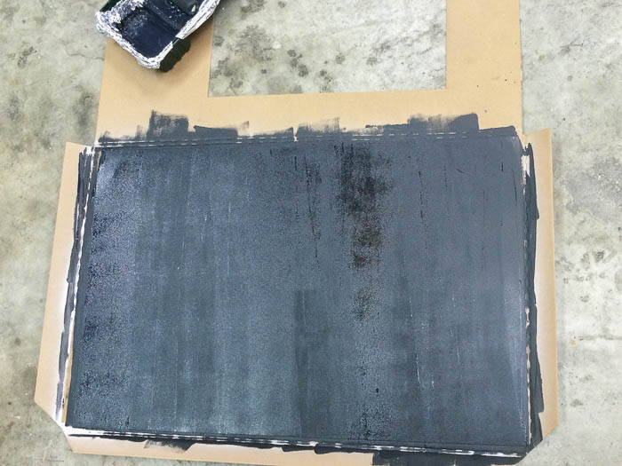 Painting galvanized metal sheet with chalkboard paint using a roler to make a DIY magnetic chalkboard