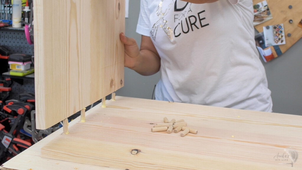 attaching the sides of the table. to the top using dowels and wood glue