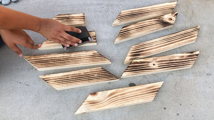 sanding boards between passes of wood burning