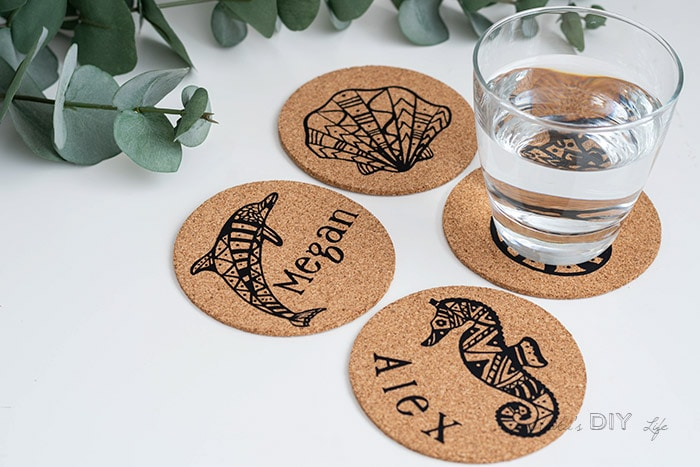DIY cork coasters with cup of water on white table