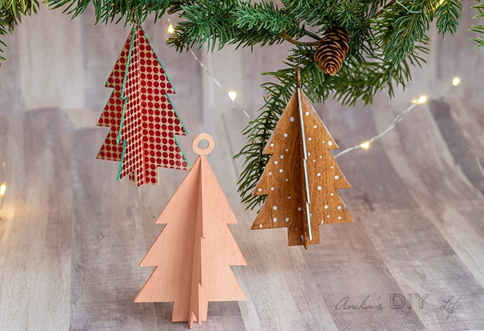 DIY Christmas tree shaped wooden ornaments hanging from branch