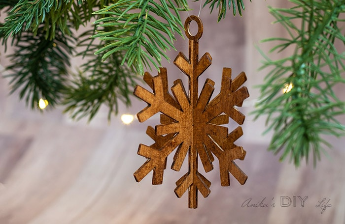 DIY wooden snowflake ornament hanging between branches.