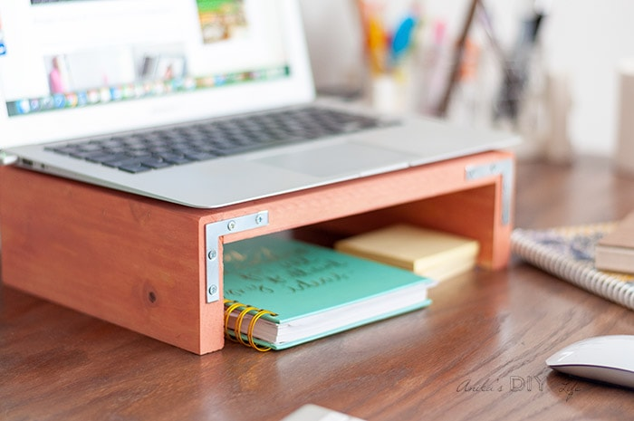 Coral laptop stand with laptop on top on a desk
