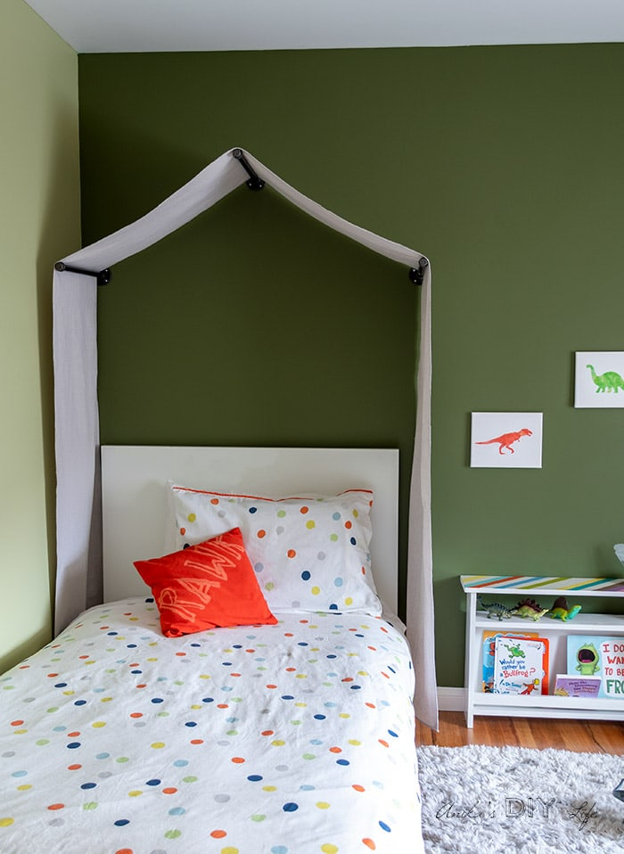 Toddler room painted dark green with tent canopy and dinosaur theme