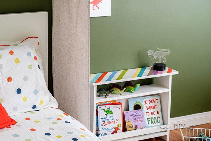 Kids bed and bookshelf in a dinosaur themed room