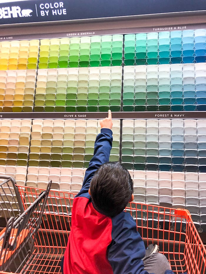 boy picking colors from wall at Home Depot