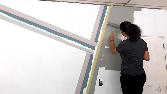 Woman painting dark grap color on the remaining wall