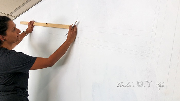 Woman Marking lines to paint a striped wall