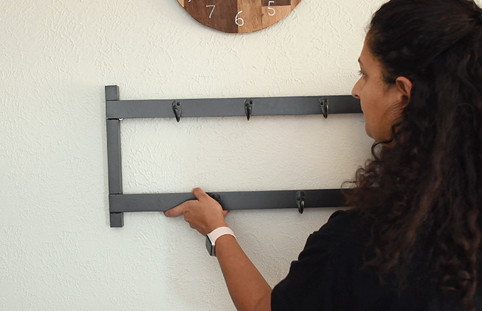 woman hanging up the metal coat rack