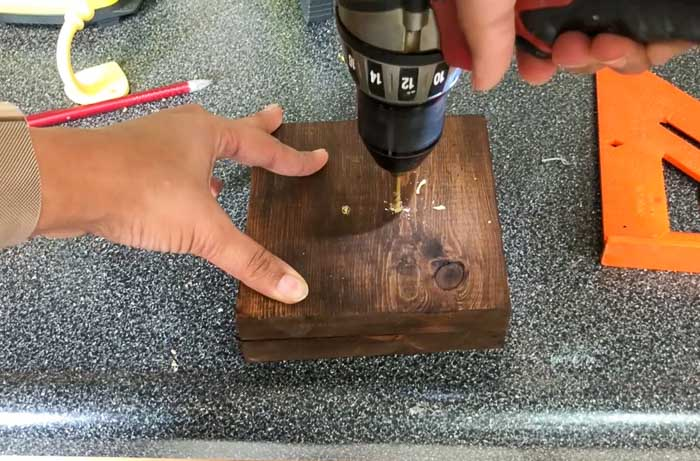 drilling pilot holes in wood boards to install hooks