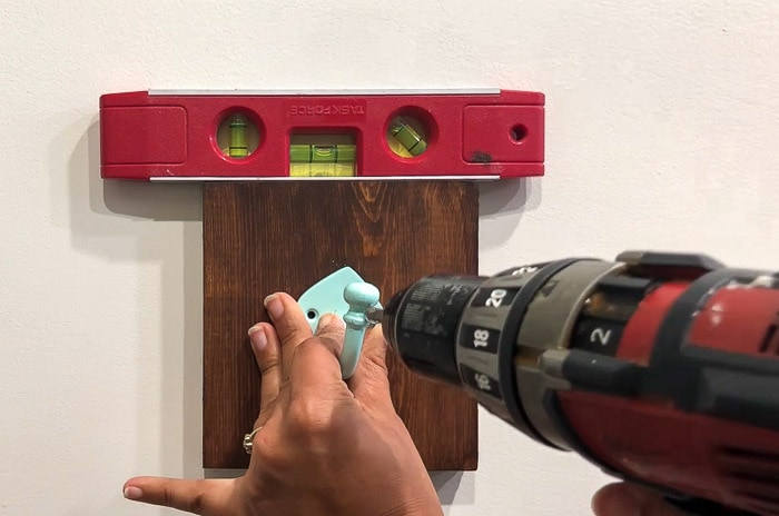 installing hooks into the wood board and into the dry wall