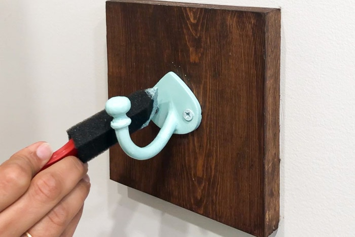 touching up paint on the diy towel hooks in bathroom