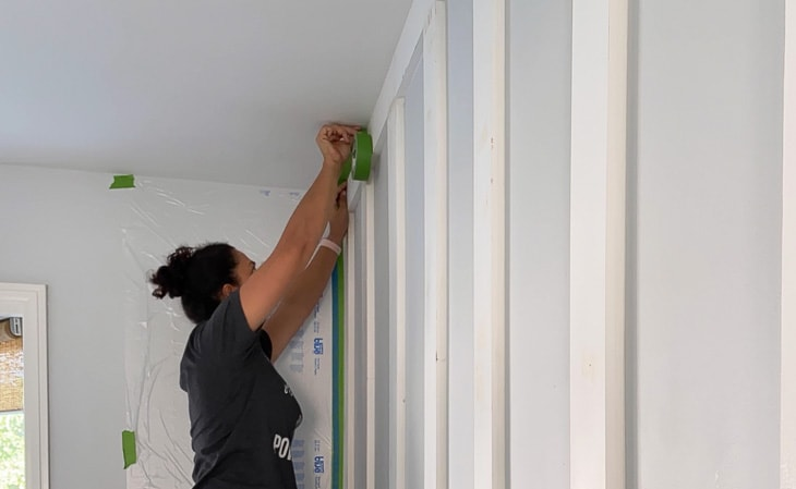 applying painters tape to paint board and batten wall with paint sprayer