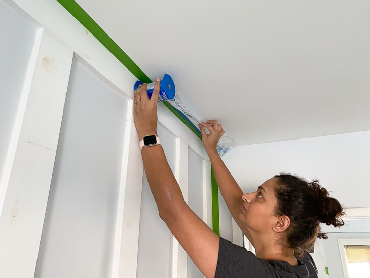 applying painter's plastic to prepare to paint a DIY board and batten wall