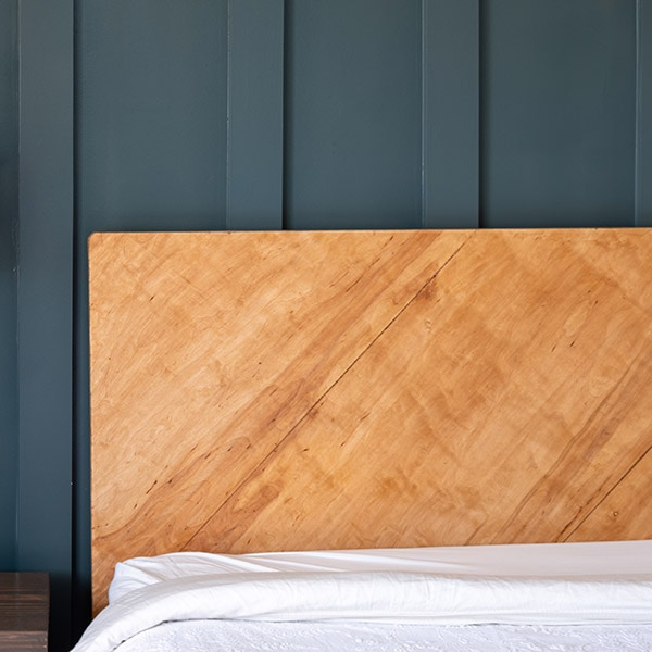 This simple and easy DIY plywood headboard is made with one sheet of plywood and a few 2x4s. Learn how to make a headboard in a weekend.