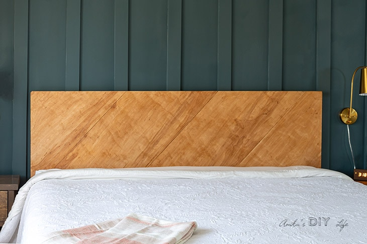 Plywood headboard against dark wall.