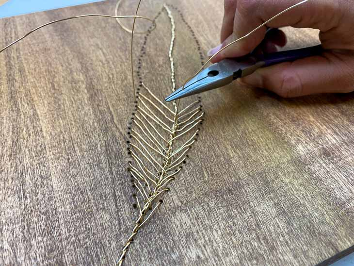 Making the vane of the feather wall art with wire on wood