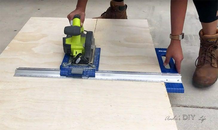 Woman using a circular saw and Kreg rip cut to cut plywood