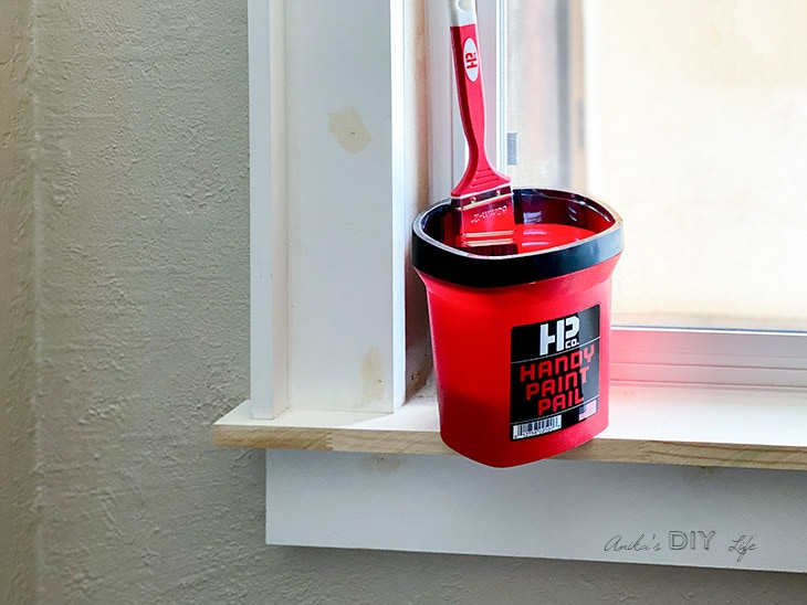 Handy Paint Pail with brush on an unpainted window trim